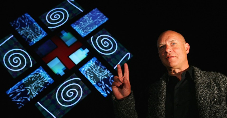SYDNEY, AUSTRALIA - MAY 26:  Artist and music producer Brian Eno poses in front of his latest light illustration titled '77 Million Paintings' during a photo call for 'Luminous', a program of musical events being hosted by the Sydney Opera House as part of Vivid Sydney on May 26, 2009 in Sydney, Australia. The festival runs from today until June 14 and sees 30 musical acts, performances and installations taking place at Bennelong Point, including Eno's audio-visual piece '77 Million Paintings' at Sydney Opera House on May 26, 2009 in Sydney, Australia.  (Photo by Sergio Dionisio/Getty Images)