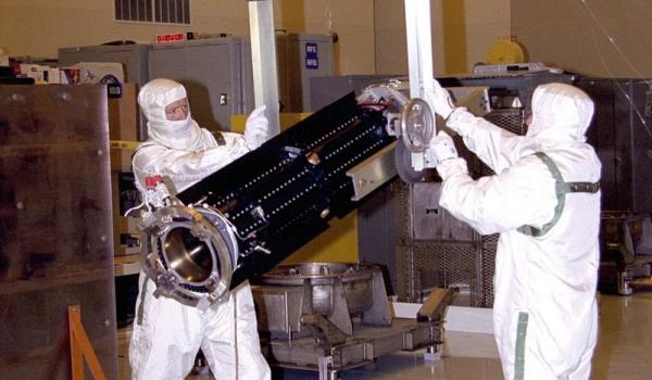 Jet Propulsion Laboratory workers handle a radioisotope thermoelectric generator (RTG) for the Cassini spacecraft mission to the Saturnian system - (Credits: NASA/JPL).