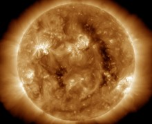 "The long dark ""gap"" in this image is a coronal hole through which solar wind escapes (Credits: SDO/AIA)."