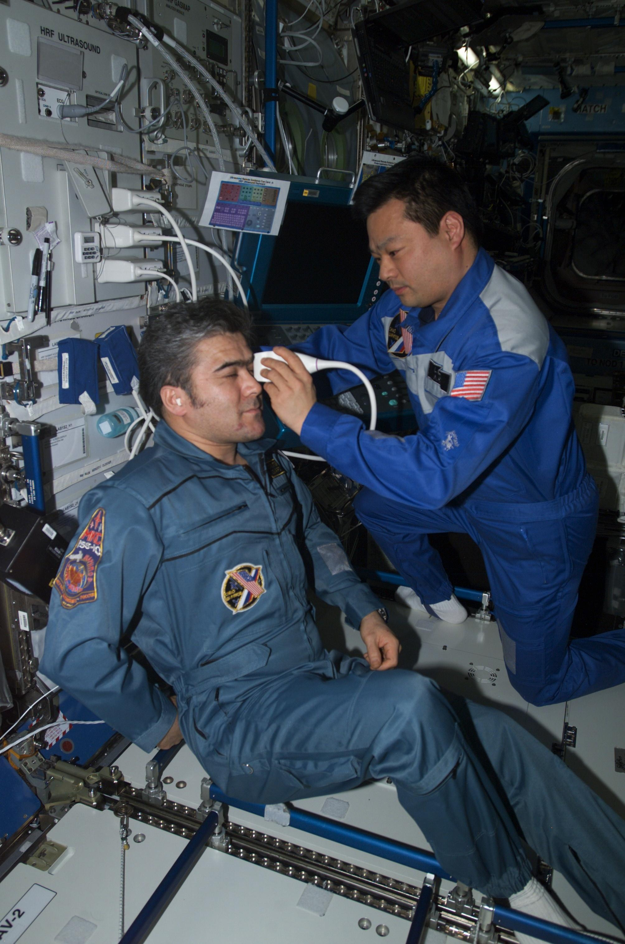 ISS Commander Leroy Chiao performs an ultrasound scan on the eye of Flight Engineer Salizhan Sharipov during ISS Expedition 10 (Credits: NASA).
