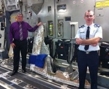 Dan Reichel, left, and Captain Raymond Scholz stand in the C-17 with a portion of recovered Atlas V casing as they prepare to fly back to the US. (Credits: Simon Jones, Bermuda Sun)