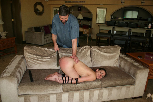 Ten Amorette is tied up in bondage for a naked paddling and strapping