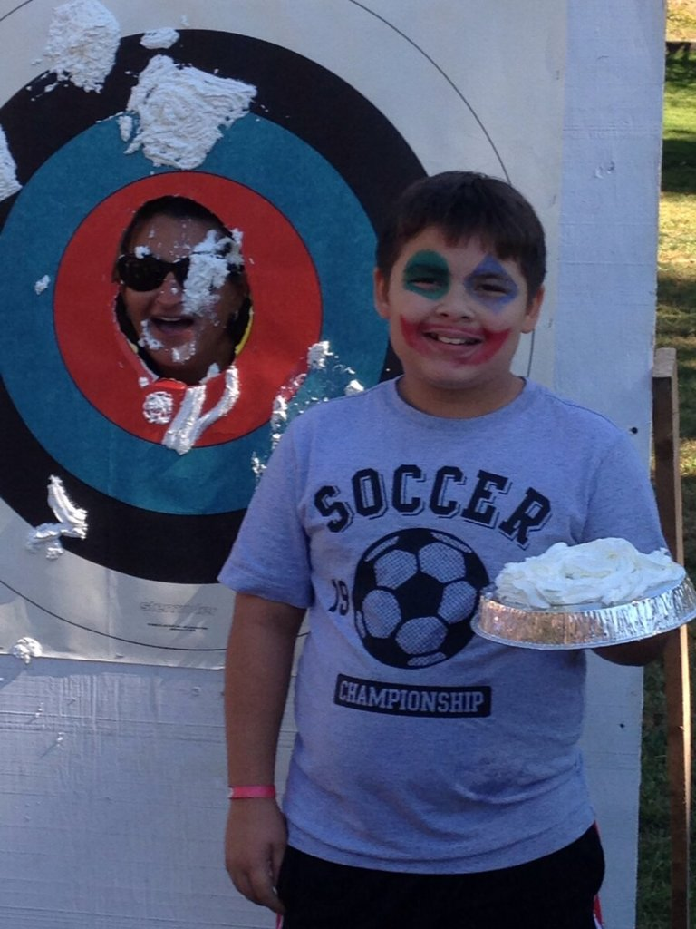 Konstantinos Parsenios helped to raise money for St. Basil's Academy as Evellyn Tsiadis rakes a pie in the face for $100.