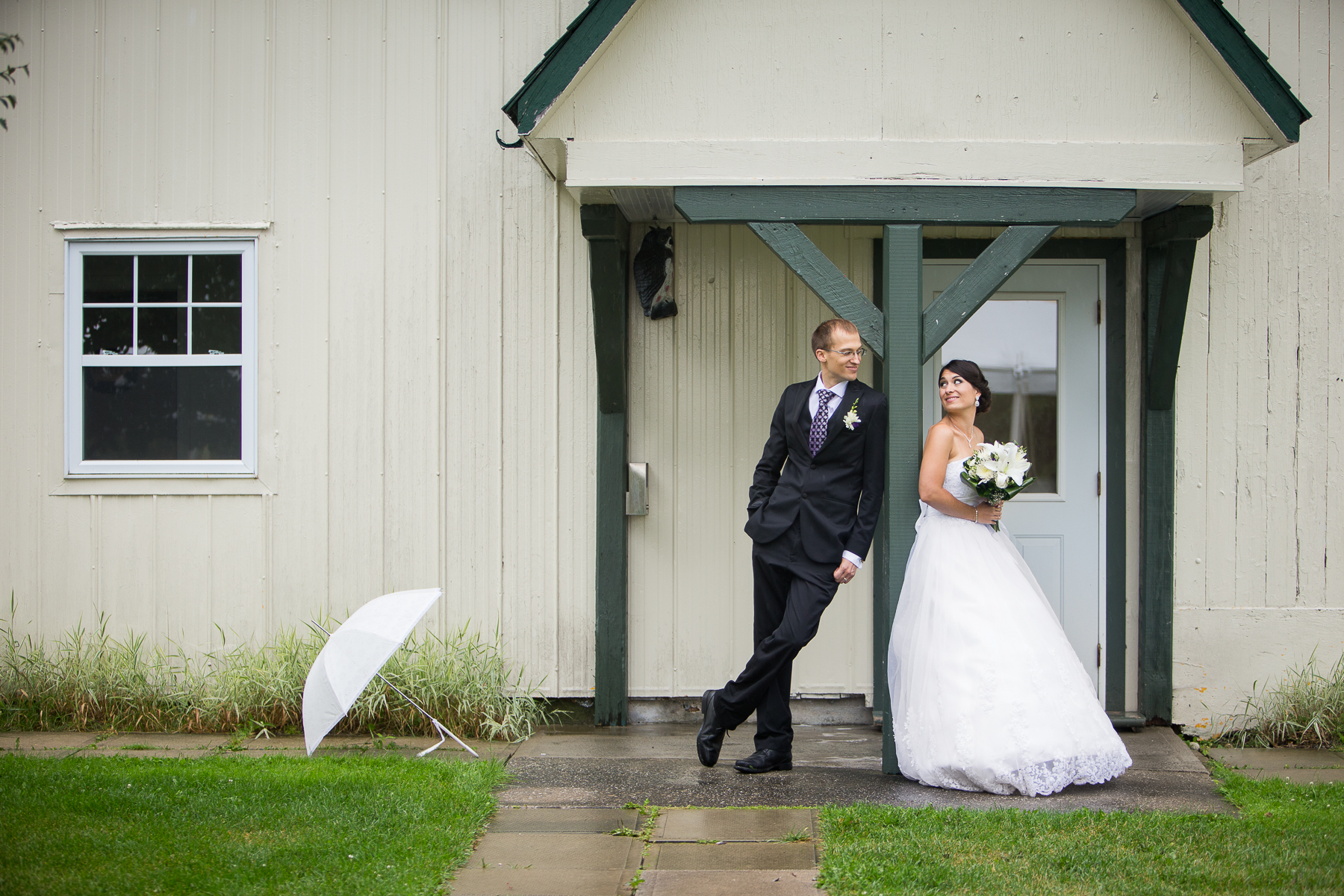 stephane-lemieux-photographe-mariage-montreal-portfolio-159-barn-couple-flowers-holding-looking-each-other-smiling-standing-umbrella-wedding