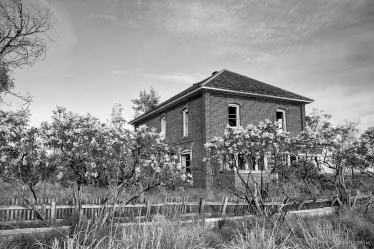 A black and white photograph of old abandoned brick house on D Road NW in rural Douglas County, Washington.