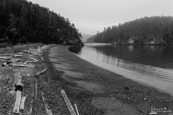 A black and white landscape photograph of the beach along Bowman Bay on a foggy Summer morning at Deception Pass State Park, Washington.