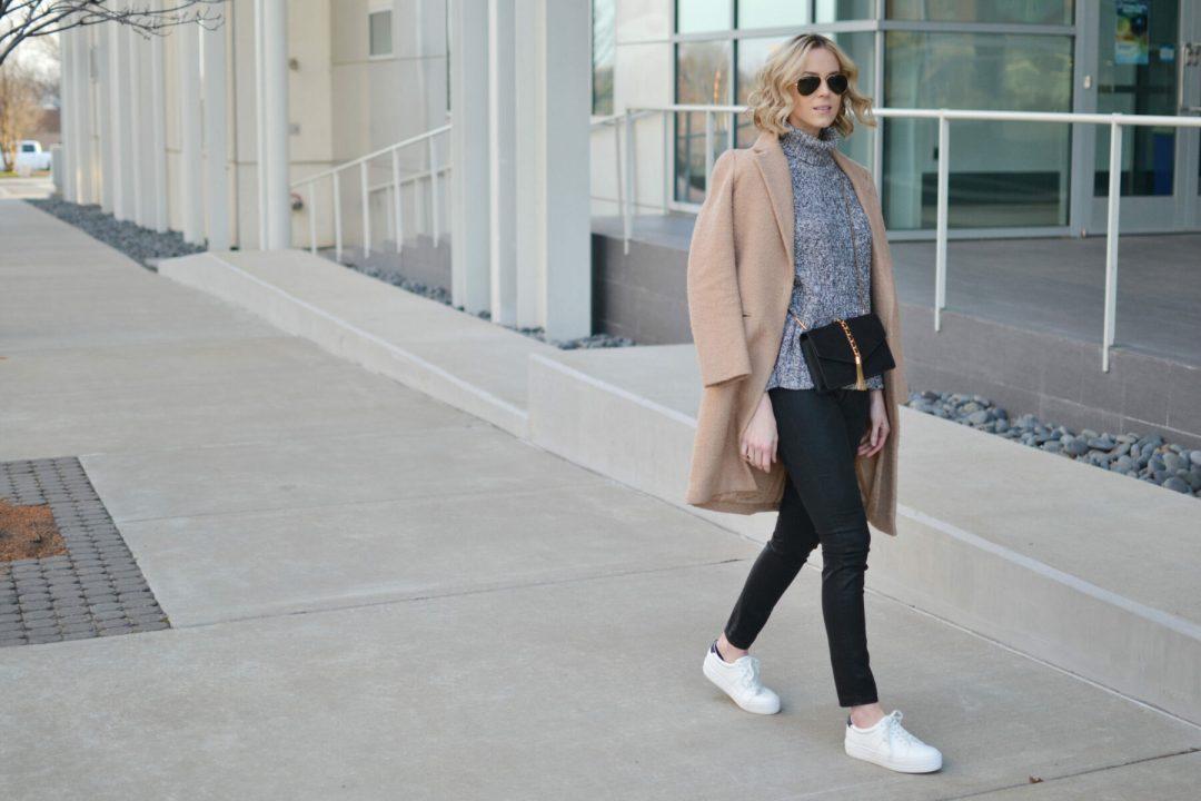 tan coat, grey turtleneck, coated black jeans, white tennis shoes