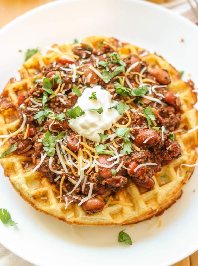 Chorizo Chili with Jalapeño Cornbread Waffles is perfect for game day, a chilly fall night or neighborhood potluck. This beefy flavored packed chili gets a slight kick from the spicy chorizo sausage. Served on top of cornbread waffles, dolloped with cheese and cilantro, and you've got yourself a well rounded meal! | Strawberry Blondie Kitchen