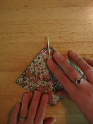 Turn paper so one corner points up and place toothpick in center of paper.