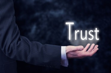 The arm of a businessman holding the word Trust.