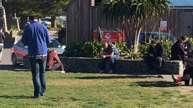 Pokemon Go players absorbed in their game at Cave Rock, Sumner, Christchurch.