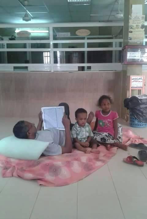 بالصورة : سوداني يفترش الأرض مع أطفاله بإحدى صالات مكاتب شركات الكهرباء بسبب إنقطاع التيار بمنزله !