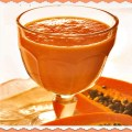 Glass of fresh papaya smoothie with sliced papaya