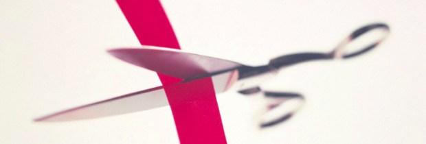 Scissors cutting a red band