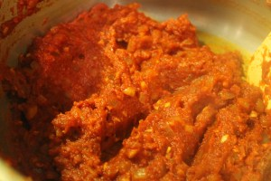 The tomato paste turns burnt orange as you cook it because you're cooking the sugars in to tomato.