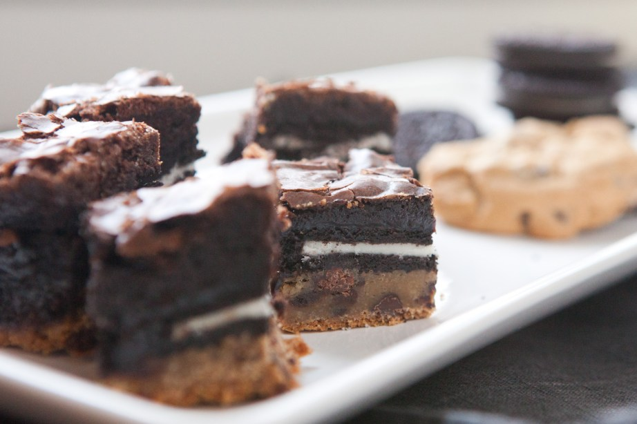 three layer brownies with cookies in background