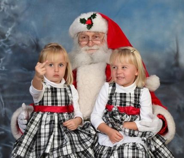 Girl Giving Finger on Santa's Lap ~ 25 Funny, Creepy Family Christmas Photos