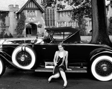 1920s flapper sitting on running board of car, gross pointe, mi