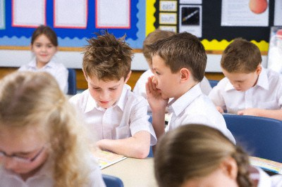 School boys whispering secrets in classroom