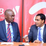 Airtel Kenya CEO Adil El Youssefi explains to UBA Kenya Bank Ltd Managing Director and CEO Isaac Mwige what the Airtel Money PESA Card offers to Airtel Money customers.