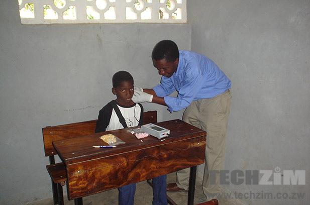 Tendekayi Katsiga working with a hearing impaired child.