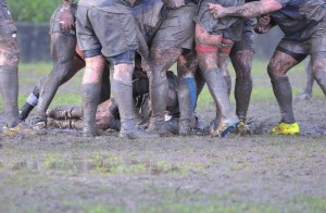 Detail muddy boots in a rugby match.