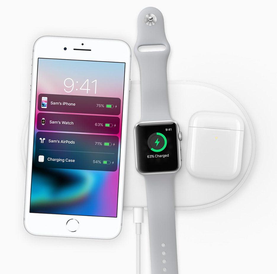 O iPhone 8 sobre a base sem fio de recarga de bateria, ao lado do Watch e dos fones Bluetooth da emrpesa