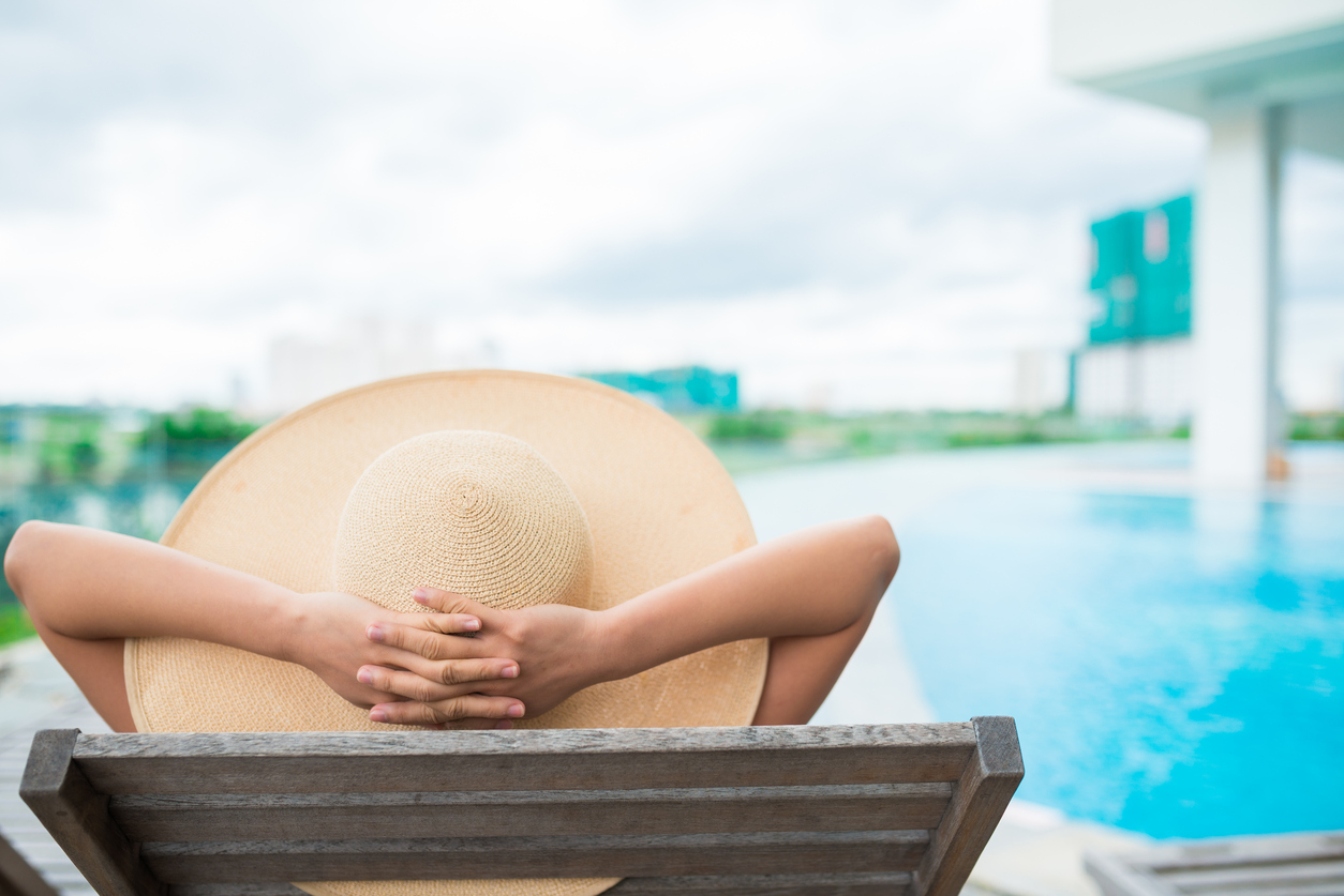 Unrecognizable woman in a big hat relaxing by the swimming pool