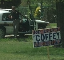 Charles County Md. Sheriff Rex Coffey on his way to secure a sign while in uniform and driving a county police car.