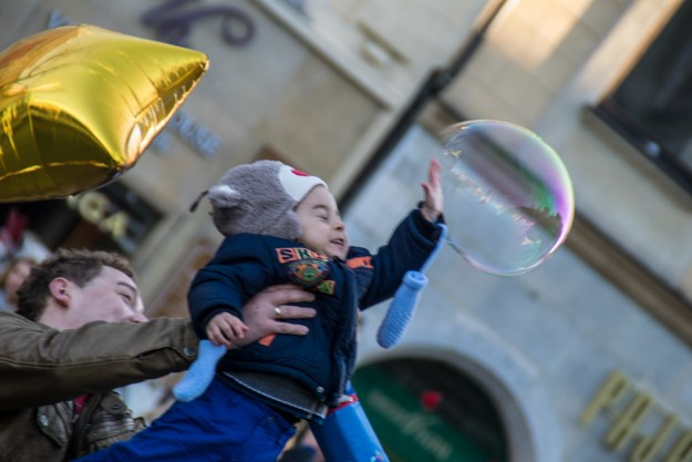 A father lifts his son up in the air to burst a soap bubble in Krakow, Poland