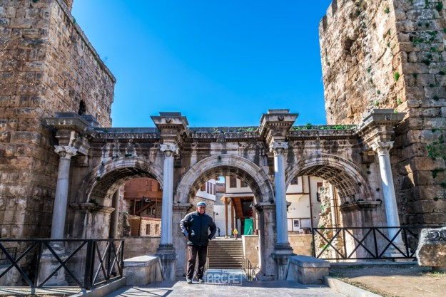 A man poses for me in front of the Hadrian Gate.