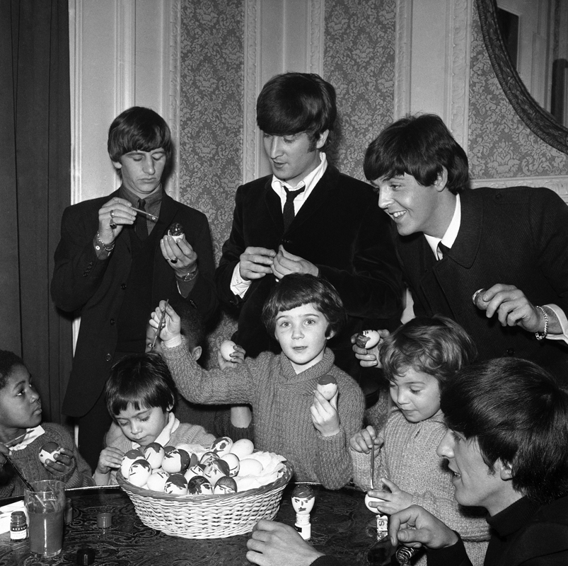 The Beatles provide both inspiriting and instruction for Church of England ChildrenÕs Society orphans as they paint mop topped Easter eggs during a visit with the Beatles at LondonÕs Scala Theatre, in England, on March 25, 1964, where the pop group is currently filming scenes for their first motion picture. Beatles from left are Ringo Starr, John Lennon, Paul McCartney and George Harrison. (AP Photo.)