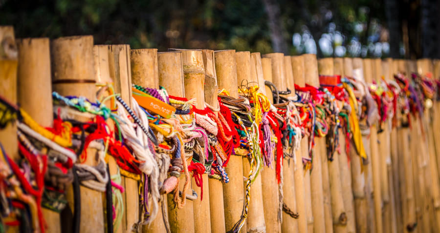 Visitors to the killing fields have placed bracelets along the fence that marks the grave sites.