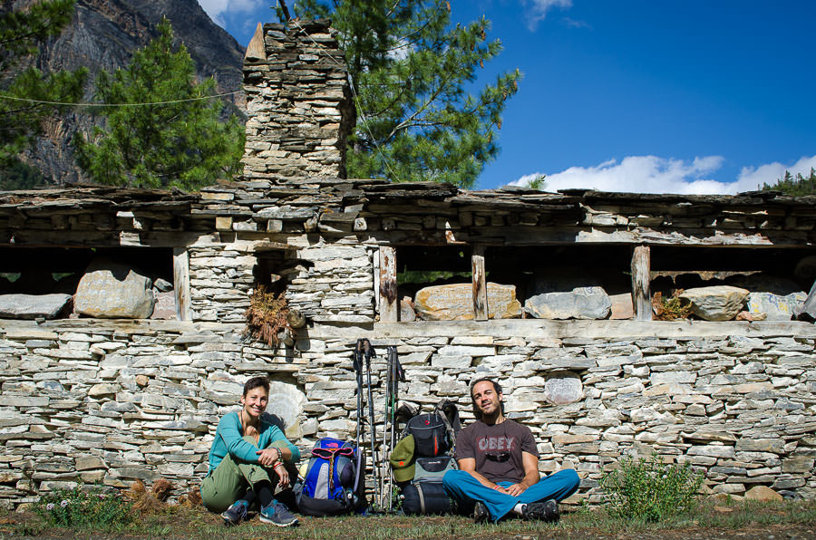 Ashlie and Adrian taking a rest against a mani wall on the Annapurna Circuit