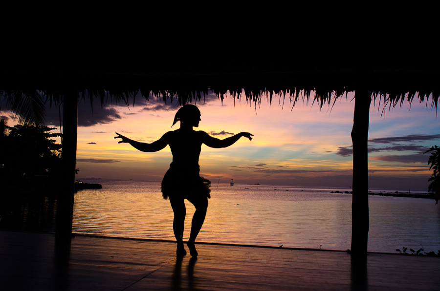 Girl dancing with the sunset behind her