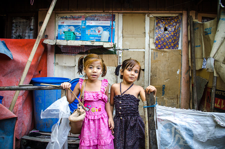 Two young girls in front of their house that is taped up with cardboard