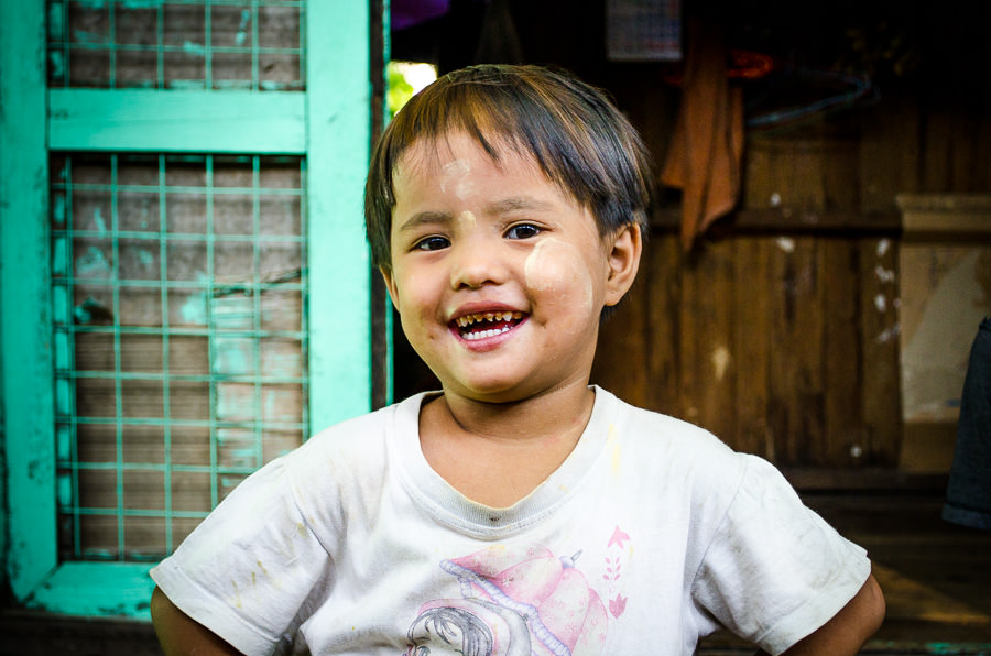 Young girl standing in front of her home in Myanmar.
