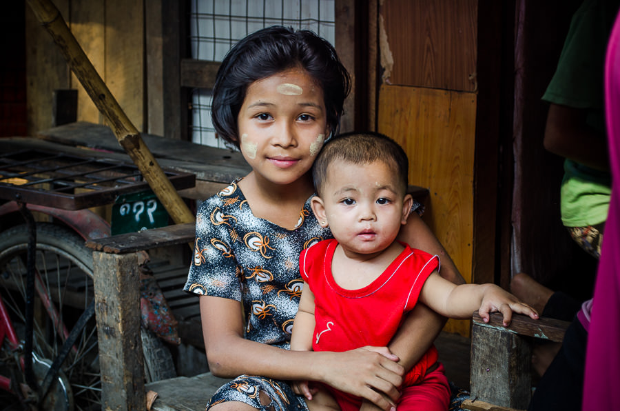 Young girl sitting on her porch holding her younger sibling. Myanmar.
