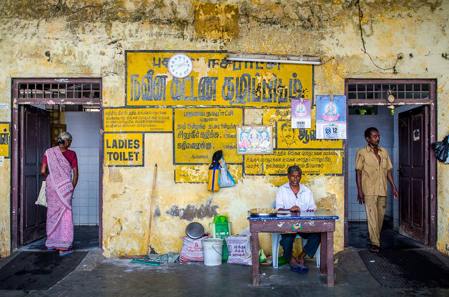 A bathroom clerk at a bus stand in India