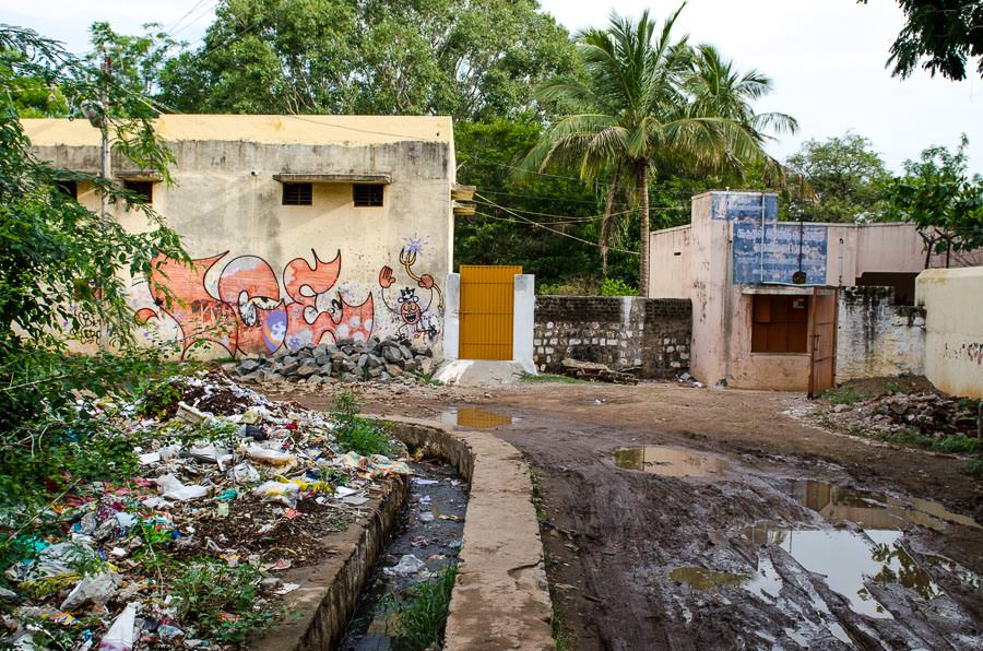 A muddy, trashy alleyway in Tiruvannamalai, India