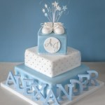 Christening cake with boxes and baby shoes.