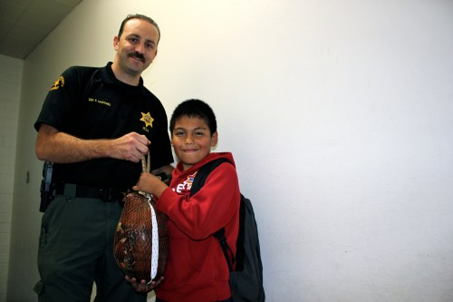 San Juan Capistrano Sheriff's Deputy Felipe Martinez and San Juan Elementary School fifth-grade student Jaime Ramirez hold up a turkey Ramirez earned as part of the Orange County Gang Reduction Intervention Partnership's Thanksgiving incentive program. Photo by Brian Park