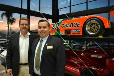 San Juan Capistrano Mazda dealership co-owner Miles Brandon (left) and Mayor Sergio Farias (right) stand in front of Mazda race cars featured at the dealership's ribbon-cutting ceremony on Thursday, Feb. 1. Photo: Emily Rasmussen