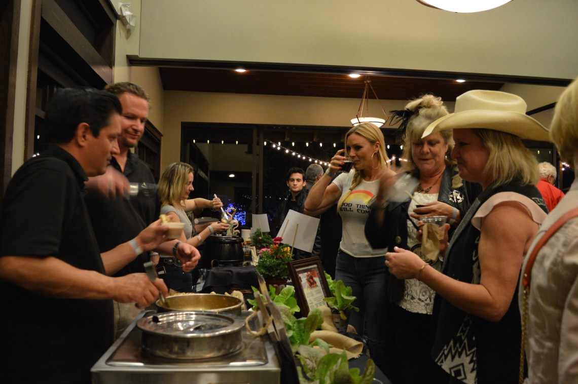 Attendees try a sampling of Trevor's At The Track's 'Wok the Wok' curried cioppino, which won Best Original Dish in the People's Choice Awards. Photo: Emily Rasmussen