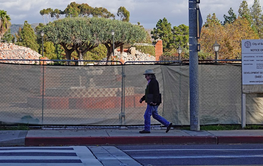 A pedestrian walks past the site for Hotel Capistrano by Kimpton on Nov. 30. Visible behind the fence is a fountain that is to be preserved, along with piles of rubble from former buildings on the site that were leveled in February, 2017, to clear the way for the hotel. Photo: Fred Swegles