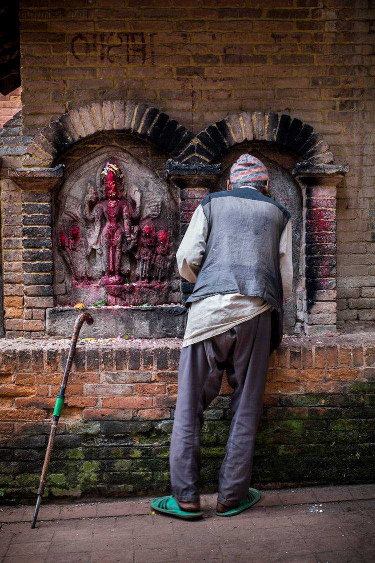Early morning in Bhakatpur, an old man prays to a idol.f/4.5, 1/50 sec, at 35mm, 400 ISO, on a X-Pro1