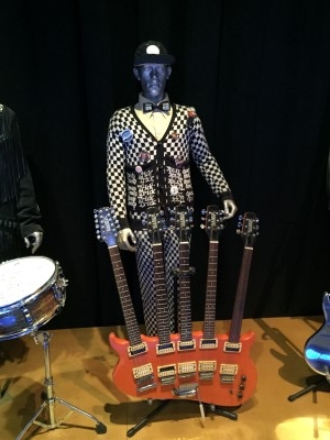 Cheap Trick's Rick Nielson's outfit and guitars on display.