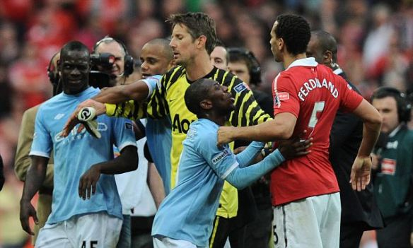 Mario Balotelli of Manchester City winks at Rio Ferdinand of Manchester United after a full time melee
