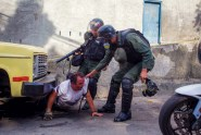 Members of the Venezuelan National Guard seize a man during anti-government protests in Venezuela recently.