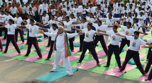New Delhi: Prime Minister Narendra Modi performs yoga along with thousands of others at a mass yoga session to mark the International Day of Yoga 2015 at Rajpath in New Delhi on Sunday. PTI Photo by Atul Yadav(PTI6_21_2015_000026B)
